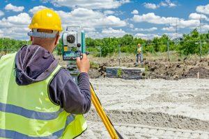 a Surveyor from Land-Mark Land Surveying Surveying a Plot of Land