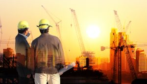 two civil engineers superimposed over the current construction of buildings as the sun sets casting a burnt yellow glow over the horizon