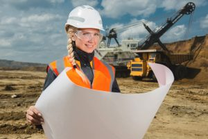 smiling female land surveyor holding plans and wearing a hard hat