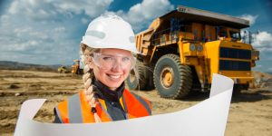 young woman wearing a hardhat and safety goggles smiling and holding a blueprint