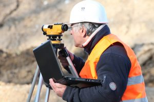 older land surveyor using a theodolite to survey land