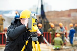 worker doing a land survey with a theodolite