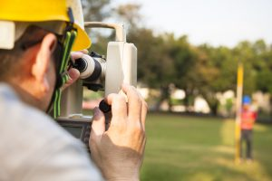 a land surveyor surveying the land of a park with a theodolite