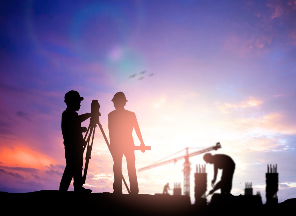 silhouette of two land surveyors with equipment against a purple sunset
