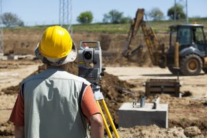 construction worker at a site with a theodolite