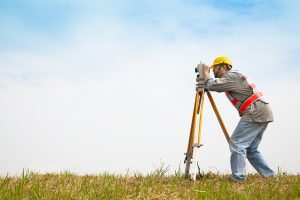 Surveyor engineer making measure onf a field