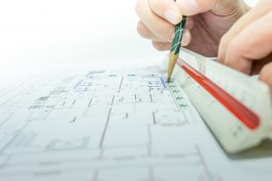 engineer using a paper, ruler, and pencil to draw blue prints