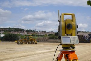 Land surveyor equipment with a developed plot in the background