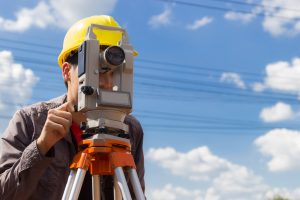 Land surveyor using equipment with blue sky in background