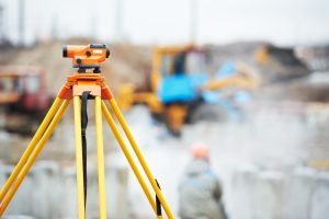 land surveyor equipment with out of focus construction in background