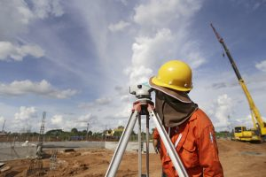 land surveyor worker working with equipment at factory construction site outdoors blue sky background