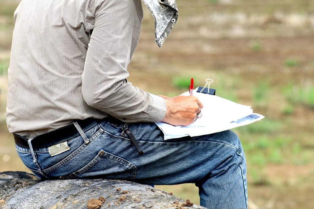 land surveyor taking notes while sitting on a rock