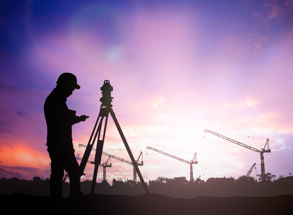 silhouette of land surveying engineer working  in a building site with a purple and white sunset background