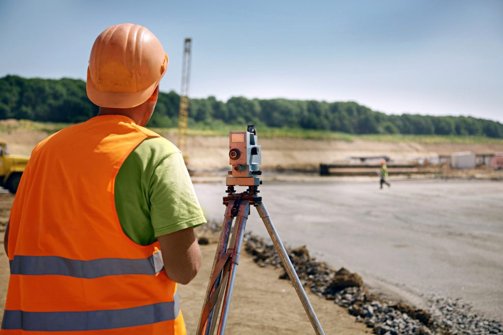 land surveyor in orange vest overlooking a piece of land with a crane in the distance