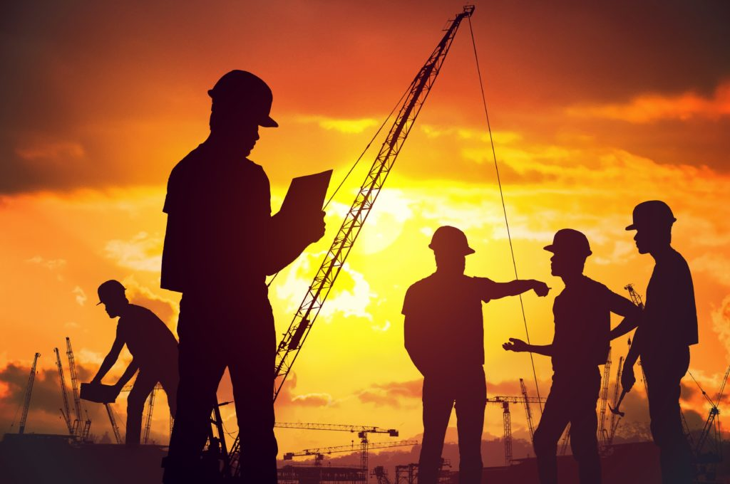 Silhouettes of workers working on construction survey at sunset