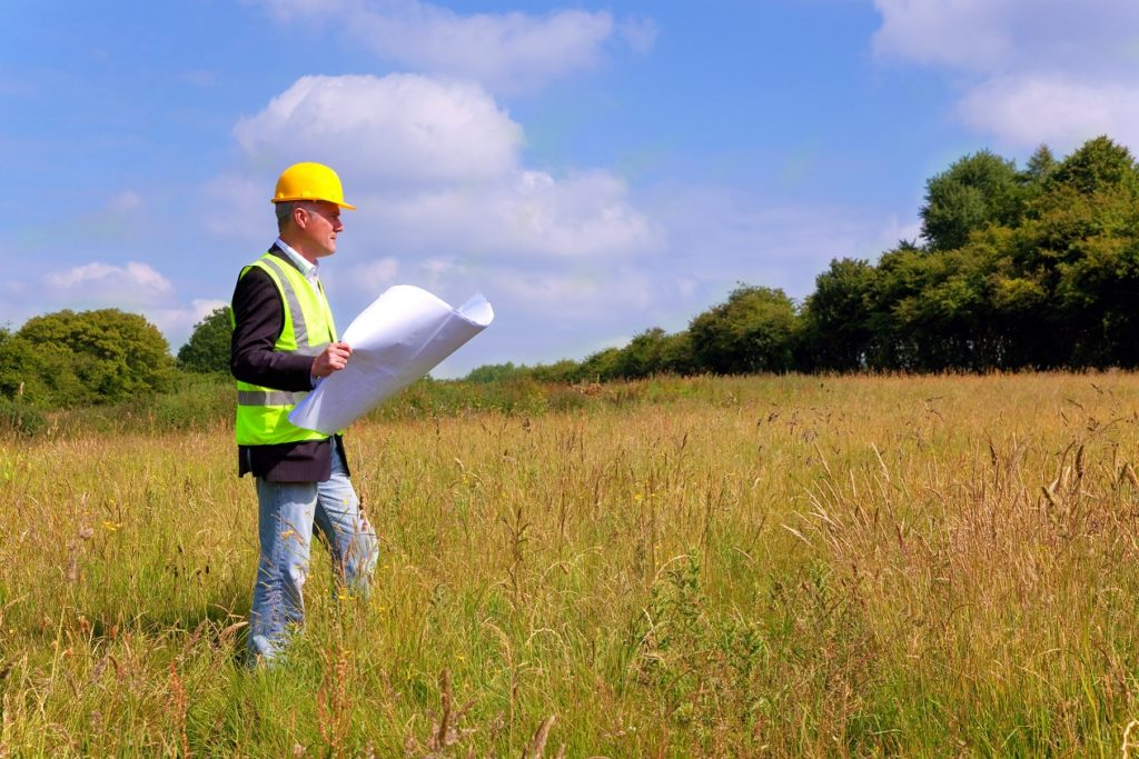 construction manager walking a grassy sight with a map, land planning for a project