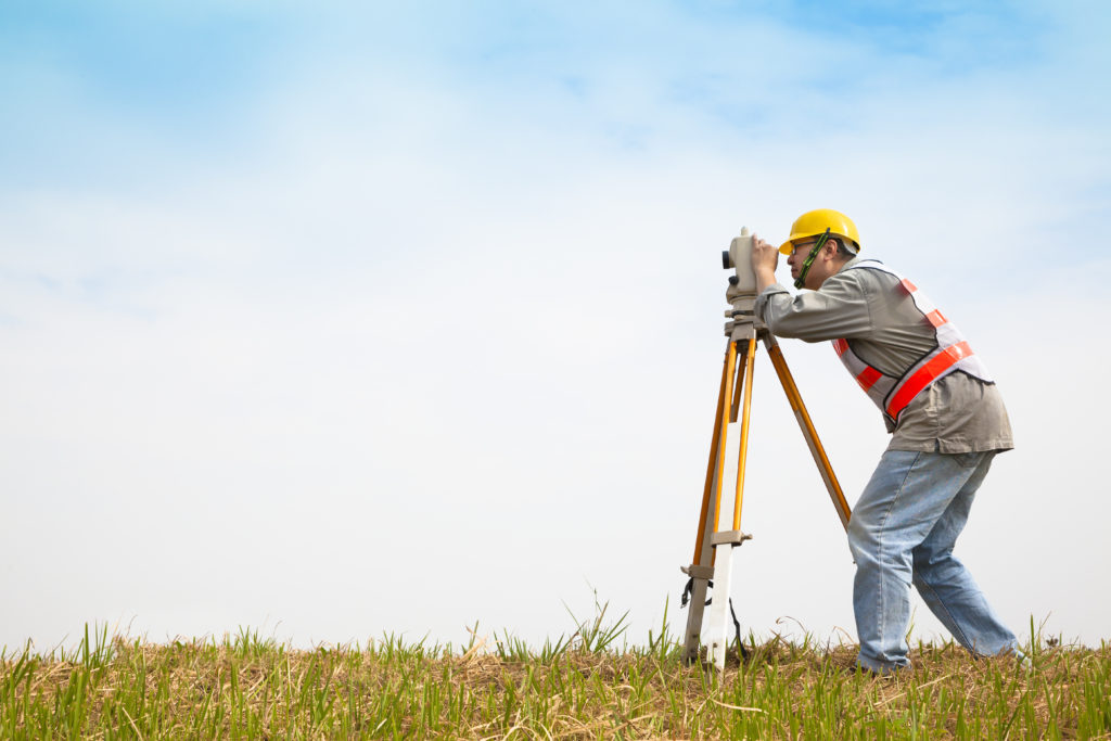 a land surveyor working with a theodolite