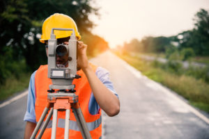 A young surveyor takes measurements on the road while the sun rises in the morning
