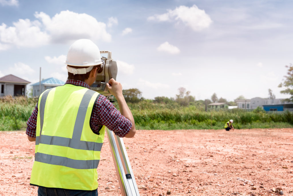 a man using a theodolite to check land