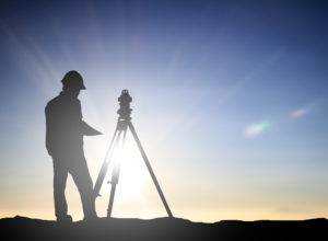 a man who is part of a group of land surveyors in silhouette next to a theodolite