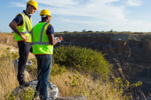 two male surveyors working at mining site